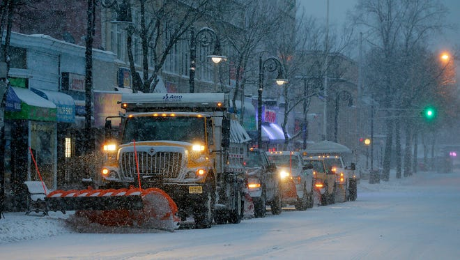 Plow trucks idle along Watchung Avenue at 7:30 a.m. during the snow storm in Plainfield on Tuesday.