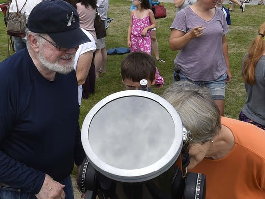 Mike Egan of the Door Peninsula Astronomy Society helps people view the solar eclipse with the help if his telescope Monday, Aug. 21, 2017, at the Ray and Ruthie Stonecipher Astronomy Center, Sturgeon Bay. The solar eclipse program was hosted by the Door Peninsula Astronomical Society.  To see more photos, go to: www.doorcountyadvocate.com.