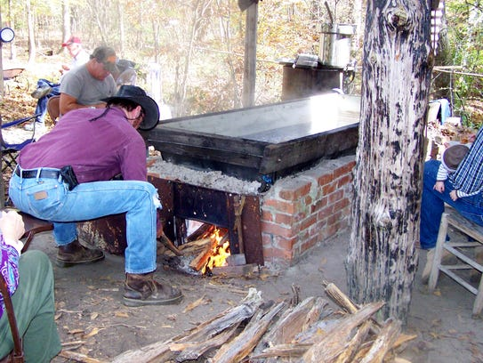 Family members Bill West and Dean Stanley make sure the furnace is at the correct temperature to cook the syrup.
