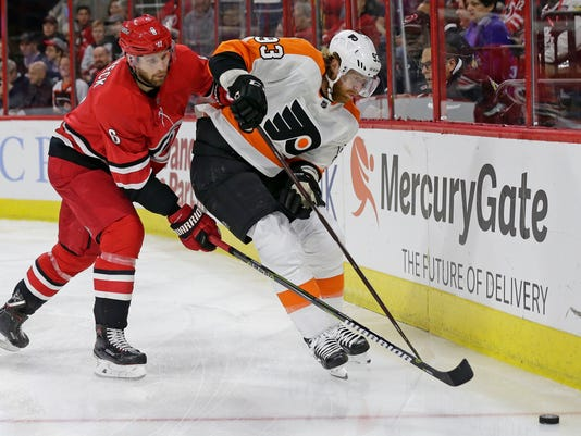 Carolina Hurricanes' Klas Dahlbeck (6), of Sweden, chases the puck with Philadelphia Flyers' Jakub Voracek (93), of the Czech Republic, during the first period of an NHL hockey game in Raleigh, N.C., Tuesday, Feb. 6, 2018. (AP Photo/Gerry Broome)