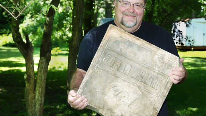 Tom Oakley holds the top half of the grave marker he found on his Brookside Drive property. Records show Luman Willard, possibly the grandfather of boxer Jess Willard, was buried in Hayesville.