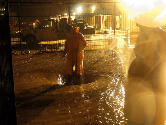 Workers keep a drainage hole from clogging on Aug. 26 near McGee Park in Farmington.