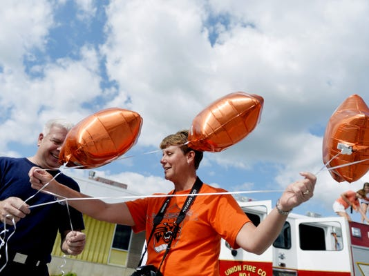 Union Fire Company firefighter Andy Stevens and volleyball parent Jodi Arentz untangle balloons in anticipation of a celebration parade in East Manchester Township for the Northeastern boys' volleyball team, following the Bobcats' third-straight PIAA Class AA state championship on June 6. The Bobcats swept Saegertown (25-9, 25-22, 25-12) in State College, and returned to a welcoming hometown crowd.