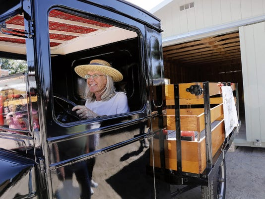 Helen Root backs up a 1927 Model TT into a garage Saturday during Sutherland Farms' Green Chile Festival in Aztec.
