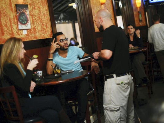Michelle Stern of Dover, left, and Tashaun Dennis of York talk with their server at White Rose Bar and Grill in York last month.