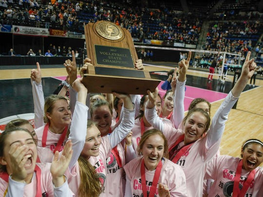 Members of the Dubuque Wahlert volleyball team celebrate a Class 4A state title win over Sergeant Bluff-Luton during the 2017 Iowa high school state volleyball tournament on Friday, Nov. 10, 2017, in Cedar Rapids.