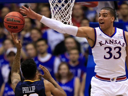 Kansas forward Landen Lucas (33) blocks a shot by West Virginia guard Tarik Phillip (12) during the first half of an NCAA college basketball game in Lawrence, Kan., Tuesday, Feb. 9, 2016. (AP Photo/Orlin Wagner)