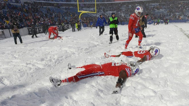 Buffalo Bills players make snow angels after beating the Indianapolis Colts after an NFL football game, Sunday, Dec. 10, 2017, in Orchard Park, N.Y. The Bills beat the Colts in overtime 13-7. (AP Photo/Adrian Kraus)