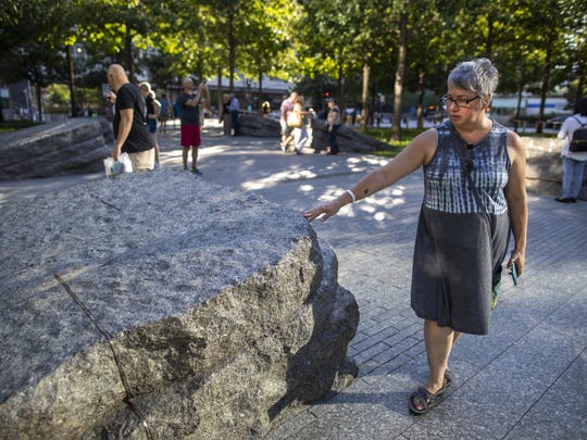 In this Thursday, Aug. 29, 2019, photo a visitor touches one of the granite slabs at the 9/11 Memorial Glade at the National September 11 Memorial & Museum in New York. When the names of nearly 3,000 Sept. 11 victims are read aloud Wednesday, Sept. 11 at the World Trade Center, a half-dozen stacks of stone will quietly salute an untold number of people who aren't on the list. The granite slabs were installed on the memorial plaza this spring. They recognize an initially unseen toll of the 2001 terrorist attacks: firefighters, police and others who died or fell ill after exposure to toxins unleashed in the wreckage. (AP Photo/Mary Altaffer)