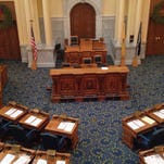 Proposed constitutional amendments sit on the desks of Assembly members in the State House on Friday.