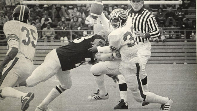 Ira Matthews (33) breaks a tackle against Belvidere during East's undefeated state champion season in 1974. Matthews also was the punt returner and kick returner for the Oakland Raiders when they beat the Philadelphia Eagles in the 1981 Super Bowl.
