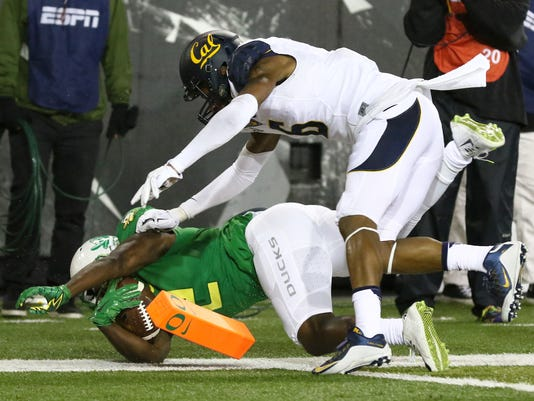 Oregon wide receiver Bralon Addison (2) scores a touchdown after being pushed by California cornerback Darius White (6) during the first half of an NCAA college football game, Saturday, Nov. 7, 2015, in Eugene, Ore. (AP Photo/Ryan Kang)