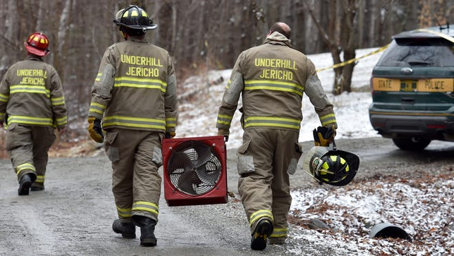 Firefighters carry a fan as rescue personnel and Vermont State Troopers gather at the site of a suspected carbon monoxide leak on Bolger Hill Road in Jericho on Wednesday, March 23, 2016.
