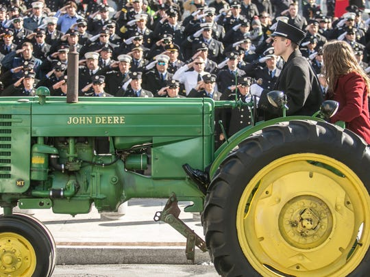 Lt. Dennis H. DeVoe's son and daughter, ride the family's antique tractor, in front of the Pennsylvania State Capital building  during the Funeral Procession Friday, March 17, 2017, in Harrisburg. Amanda J. Cain photo