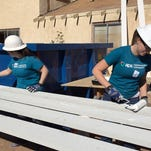 APS employees Nicole Zobrist (left) and Danielle Evans (right) work on the Vail's refurbished home in Peoria, a Habitat for Humanity project.