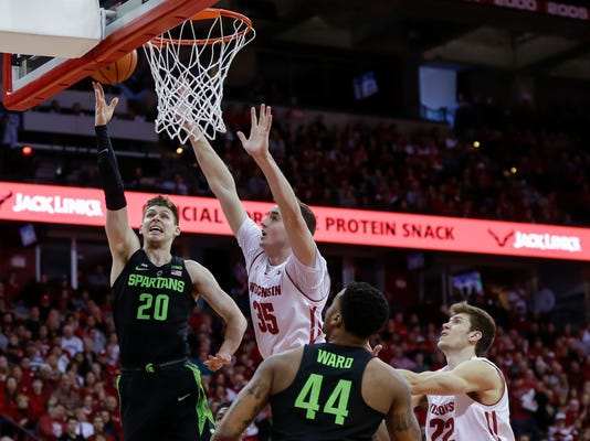 Michigan State's Matt McQuaid (20) shoots against Wisconsin's Nate Reuvers (35) during the first half of an NCAA college basketball game Sunday, Feb. 25, 2018, in Madison, Wis. Also in on the play is Michigan State's Nick Ward (44) and Wisconsin's Ethan Happ (22). (AP Photo/Andy Manis)