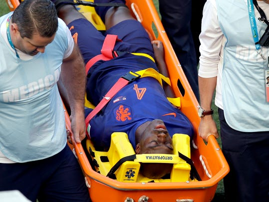 Netherlands' Bruno Martins Indi is carried off the pitch after a tackle during the group B World Cup soccer match between Australia and the Netherlands at the Estadio Beira-Rio in Porto Alegre, Brazil, Wednesday, June 18, 2014. (AP Photo/Michael Sohn)