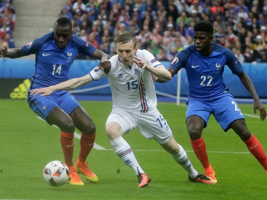 Iceland's Jon Dadi Bodvarsson, center, challenges for the ball with France's Blaise Matuidi, left,  and France's Samuel Umtiti during the Euro 2016 quarterfinal soccer match between France and Iceland, at the Stade de France in Saint-Denis, north of Paris, France, Sunday, July 3, 2016. (AP Photo/Petr David Josek)