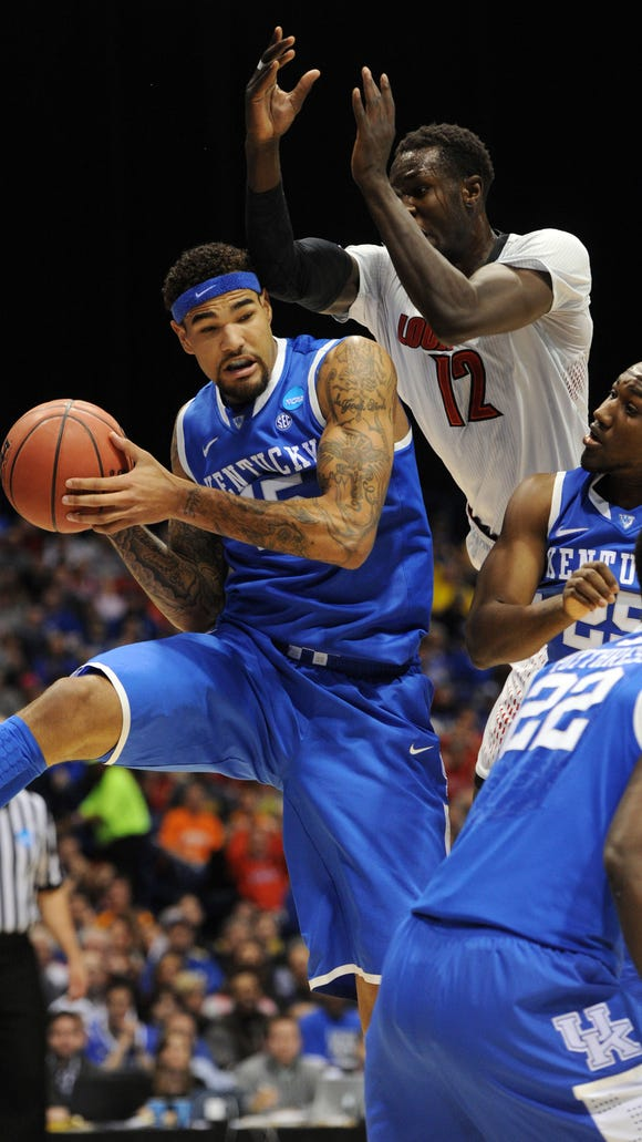 Kentucky's Willie Cauley-Stein, left, controls a rebound against Louisville's Mangok Mathiang in the first half Friday night at Lucas Oil Stadium.