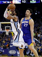 Memphis Grizzlies guard Mike Conley, left, shoots past