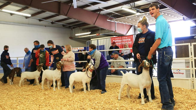 """Special Olympian athlete Grady Mercer, right, from Galena, shows """"Emily,"""" a boer goat with mentor Katie Mongeau from Finney County, during the inaugural Champions Livestock Show Friday afternoon at the Kansas State Fair."""