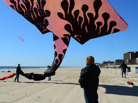 A man stands under a manta ray kite on the beach in Long Branch.