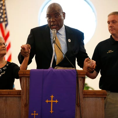 Rev. R.B. Holmes Jr., center, holds up the hands of