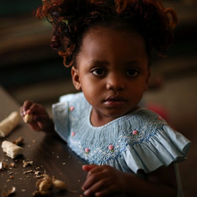 Madede Mambo, 2, eats Cassava root in the family's