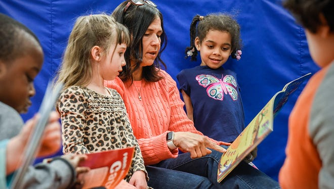 Minnesota Commissioner of Education Brenda Cassellius reads a book to preschool students Anya Vardas, left, and Serenity Schaefer Wednesday, April 25, during a visit to Westwood Elementary School in St. Cloud.