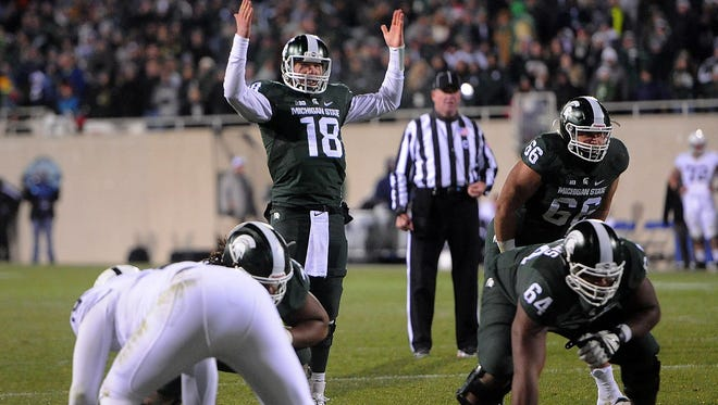 Quarterback Connor Cook raises his arms to get the crowd going in the second half of MSU's 55-16 win over Penn State Saturday, November 28, 2015, at Spartan Stadium in East Lansing.