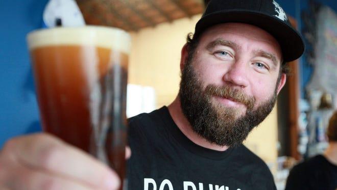 Burley Oak owner Bryan Brushmiller holds a glass of his beer.