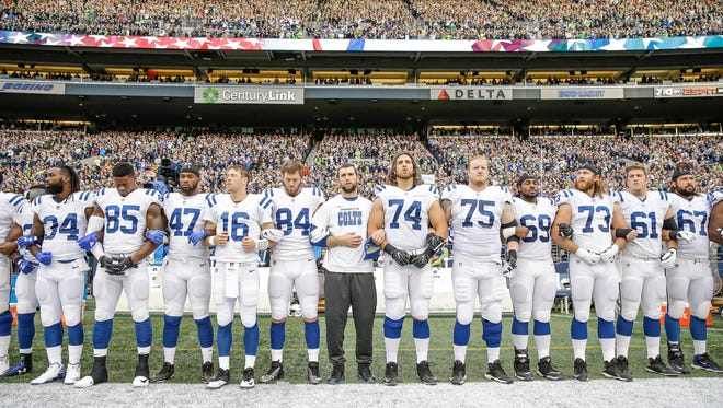 An injured Indianapolis Colts quarterback Andrew Luck (12) stands with his arms locked with Colts players before the team faces off against the Seattle Seahawks at CenturyLink Field in Seattle on Sunday, Oct. 1, 2017.