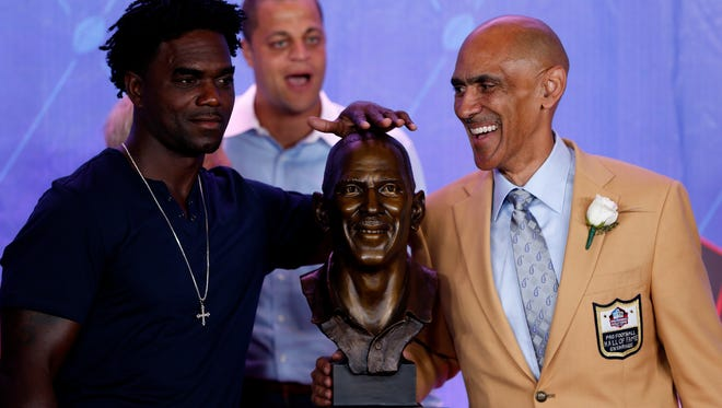 Former Indianapolis Colts running back Edgerrin James rubs the head of the bust of NFL Hall of Fame inductee and former Colts coach Tony Dungy during the NFL Hall of Fame Enshrinement Ceremony at Tom Benson Hall of Fame Stadium in Canton, Ohio, on Aug. 6, 2016.
