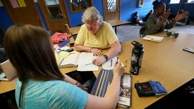 Paraeducator Carla Yenko helps sophomore Faith Harer with an assignment during lunch at Olympic High School on Monday. Yenko was named the 2018 Washington State Classified Employee of the Year by the Office of the Superintendent of Public Instruction.