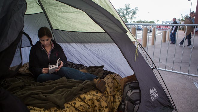 Ashley Bowers of Phoenix reads in her tent, where she will be camping out until Black Friday for the deals at Best Buy Nov. 21, 2014 in Glendale.