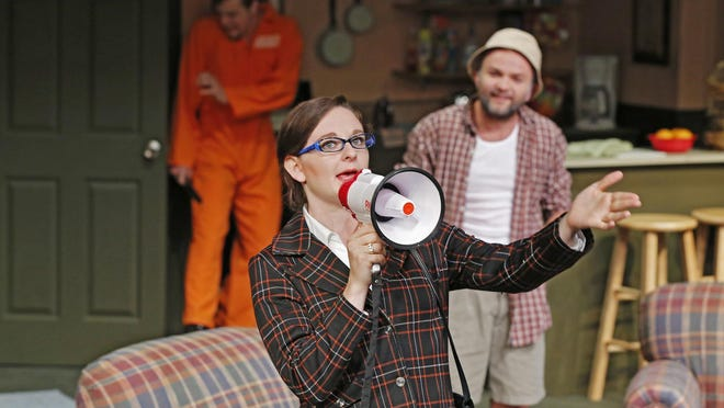 Rebecca Marowitz in the role of attorney Muriel Carlan with Jacob Gerard, background, in the role of an escaped convict and Martin Flowers, background right, in the role of Uncle Rick Deemer in Red Barn Summer Theatre's production of Death By Golf Tuesday, July 14, 2015, in Frankfort.