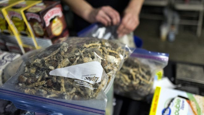 """A vendor bags psilocybin mushrooms at a pop-up cannabis market in Los Angeles on Monday, May 6, 2019. Voters decide this week whether Denver will become the first U.S. city to decriminalize the use of psilocybin, the psychedelic substance in """"magic mushrooms."""" (AP Photo/Richard Vogel)"""