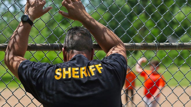 A member of the Summit County Sheriff's Office watches the action on the field from behind home plate during a whiffle ball game on Saturday in Coventry Township. Interacting with people in a community helps to foster better relations between authorities and the residents they serve, police say.