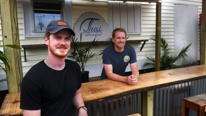 Kevin Dwyer, owner of Dwyer's Pub, left, talks about the outside dining area and new bar built by Brad Smith, right,  in Portsmouth.
