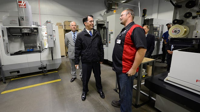 Governor Scott Walker visits with Matt Schmelzer, machine tool instructor at NWTC, during a tour of the new CNC Machining Lab at the Northeast Wisconsin Technical College in Green Bay on Friday. Walker had what appeared to be a white dressing on his right thumb, which he said he injured while pheasant hunting in Oconto County late last week.