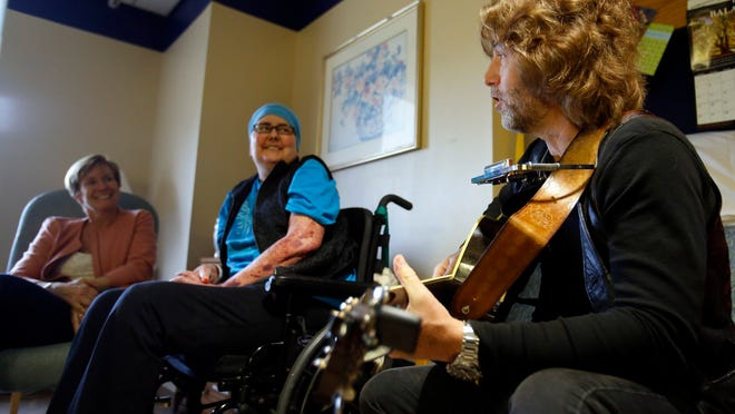 Wilmington Hospital patient Janice Ruge of Woodstown, N.J., listens as singer John Flynn performs in the Delaware debut of WXPN Musicians on Call.