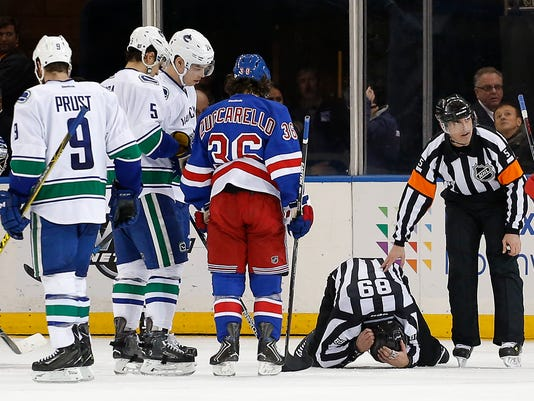 Linesman Steve Miller (89) holds his head as he kneels on the ice after he was hit by the puck during the third period of an NHL hockey game between the New York Rangers and the Vancouver Canucks, Tuesday, Jan. 19, 2016, in New York. Miller continued officiating. The Rangers won 3-2 in overtime. (AP Photo/Julie Jacobson)