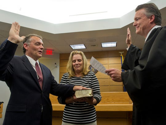 In this July 2013 photo, Brian Kirkham is sworn in by Judge Michael Jaconette as wife Diane Kirkham holds bible.