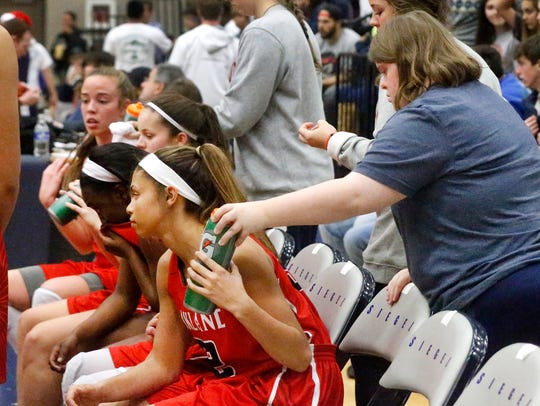 Oakland girls basketball manager Elizabeth Schott passes out water bottles during a timeout in the game against Siegel on Tuesday.