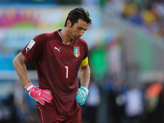 FILE - In this June 24, 2014 file photo, Italy's goalkeeper Gianluigi Buffon stands on the pitch following Uruguay's 1-0 victory over Italy during the group D World Cup soccer match at the Arena das Dunas in Natal, Brazil. The best players in the world go elsewhere. The best coaches in Italy emigrate. The stadiums around the country are falling apart. The lingering problems affecting Italy's domestic league might just be the reason for the country's failure to qualify for next year's World Cup. (AP Photo/Petr David Josek, file)