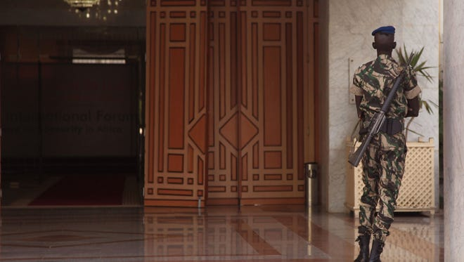 An armed Senegal soldier patrols by a doorway as Security experts gather for talks in Dakar, Senegal, Monday, Nov. 11, 2015.  Hundreds of security experts are gathered in Senegal's capital to strategize against the growing threat posed by Boko Haram and other jihadist groups in the region.