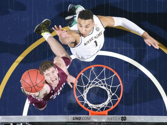 Colgate guard Sean O'Brien (0) goes up for a shot as Notre Dame Fighting Irish forward Austin Torres (1) defends in the first half at the Purcell Pavilion. Notre Dame won 77-62.