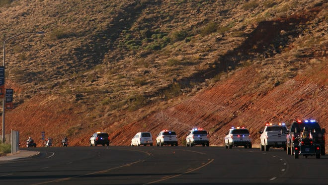 Patriot Guard Riders and law enforcement officers from a number of local agencies escort a hearse emblazoned with the star-shaped logo of the Ventura County Sheriff's Department and bearing the single, flag draped coffin in which Steve and Linda Arthur's bodies rest in St. George Monday, Sep. 21, 2015. The Arthurs were two of the seven victims killed in flash flooding in Zion Canyon last week.