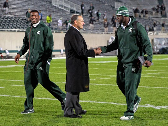 MSU coach Mark Dantonio shakes the hand of Joel Heath, right, while walking with Shilique Calhoun before the Spartans' game against Ohio State on Nov. 8, 2014.