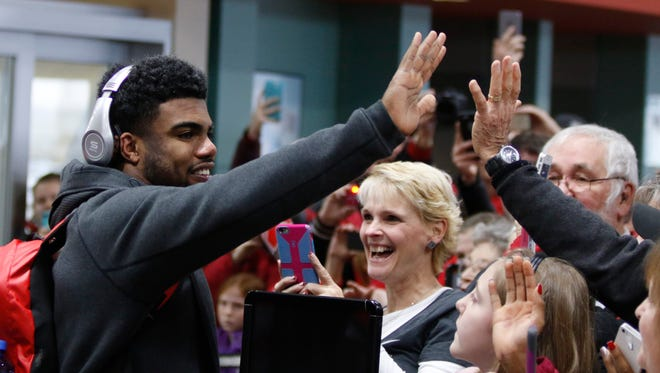 Ohio State running back Ezekiel Elliott, left, greets fans as he and his teammates arrive at Rickenbacker International Airport in Groveport, Ohio, Tuesday, Jan. 13, 2015, following a National Championship win over Oregon in Dallas, Texas. (AP Photo/Paul Vernon)
